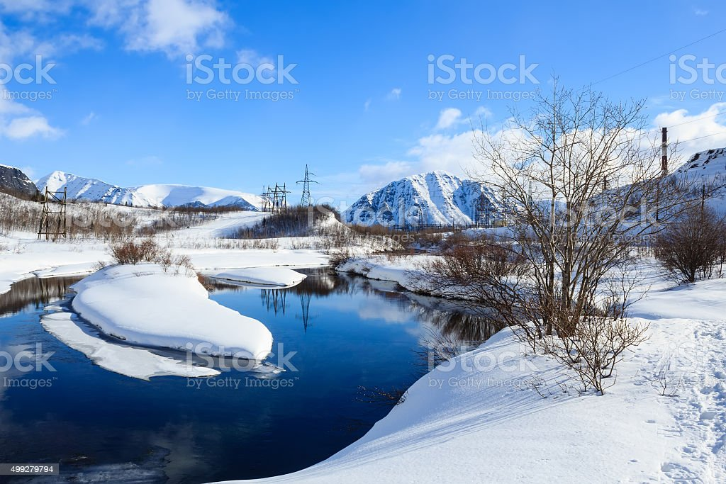 river and covered with snow banks in russian polar city stock photo
