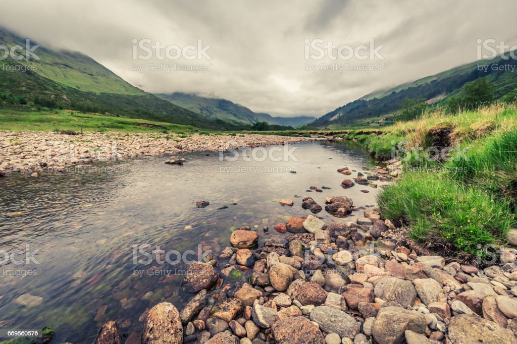 River and mountain and stones in a foggy day, Scotland stock photo