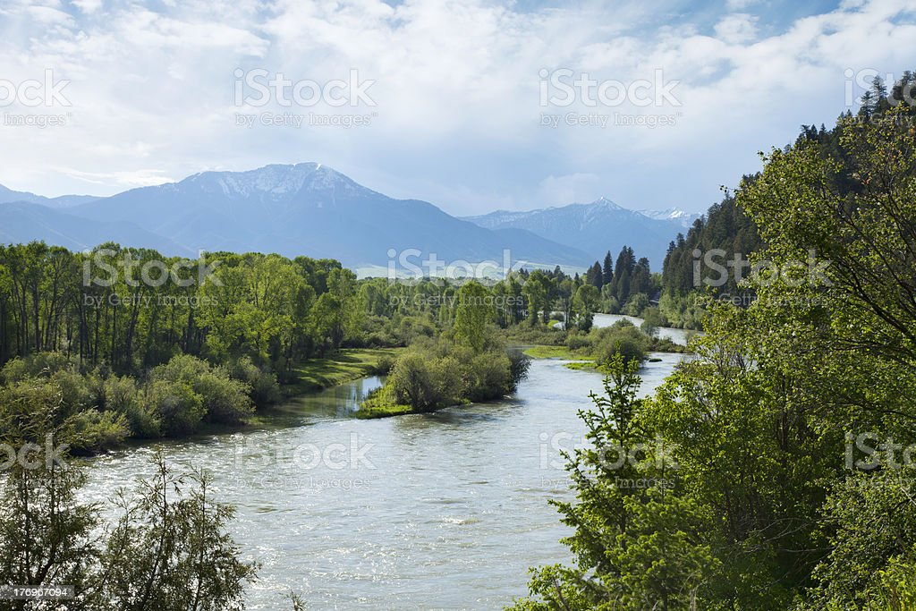 River and trees in valley with mountain backdrop royalty-free stock photo
