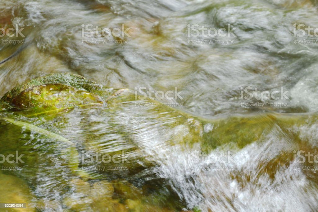 river flowing leaf stuck on cataract and make water splashing stock photo