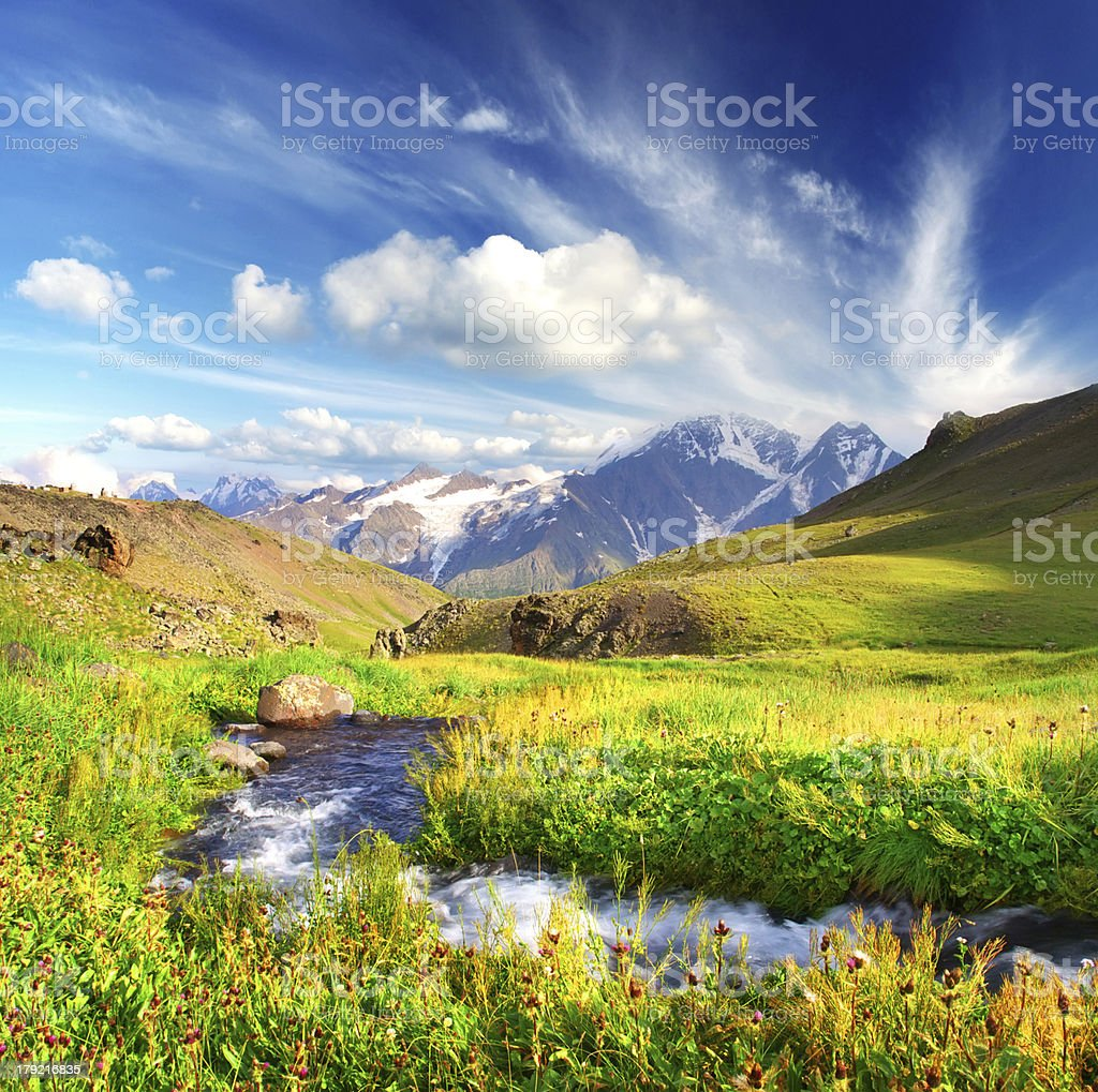 River flowing through beautiful meadow with mountains royalty-free stock photo
