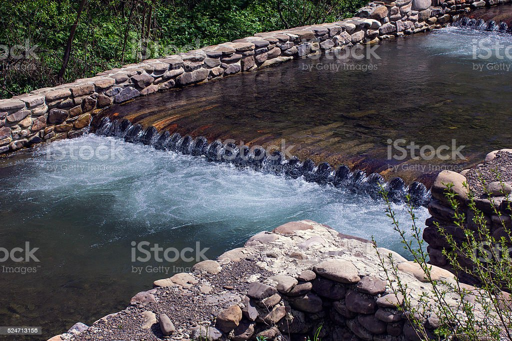 River flows through the wooden logs fenced by stone foundation stock photo