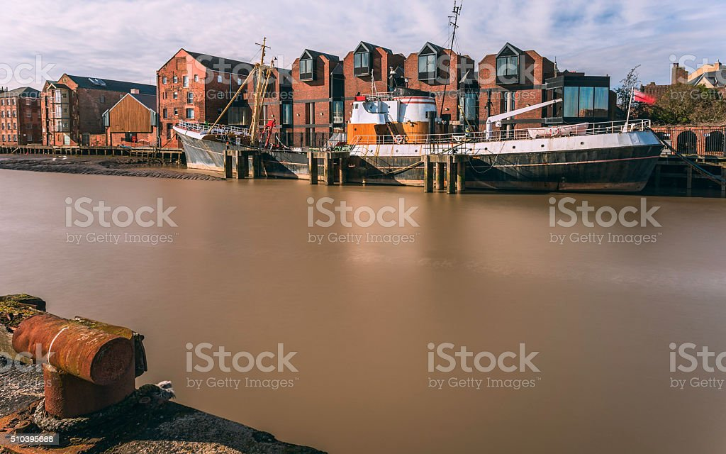 River Hull at high tide and beached obsolete fishing vessel. stock photo