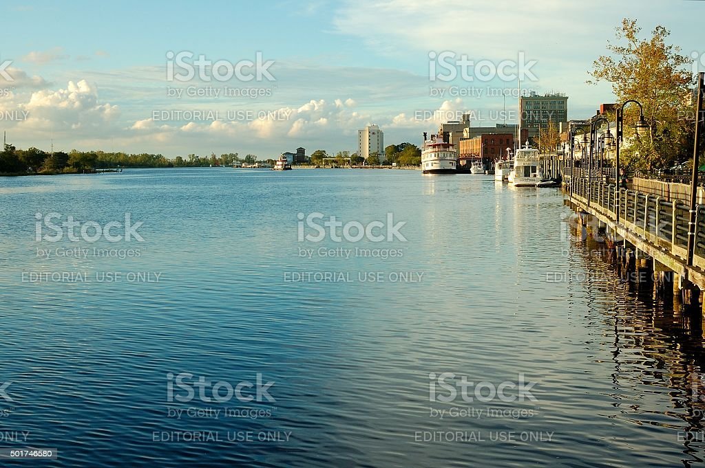 River port showing walkway and boats docked along shore stock photo