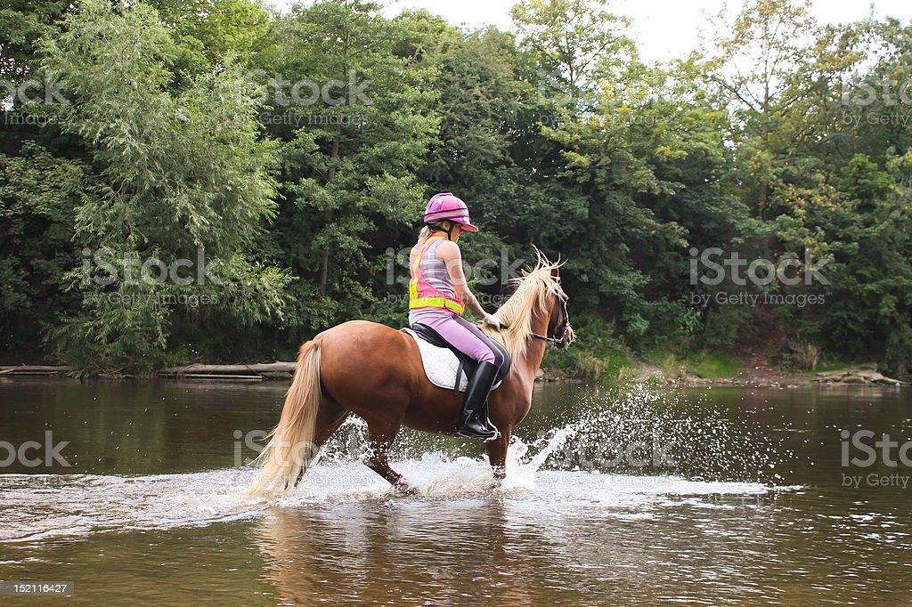 River riding-girl and her pony enjoying a summer splash royalty-free stock photo