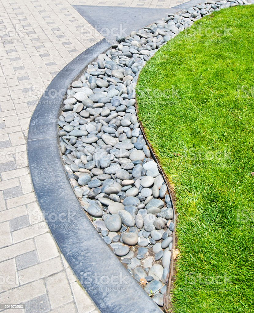 River rock stone border against fresh grass and paving bricks stock photo