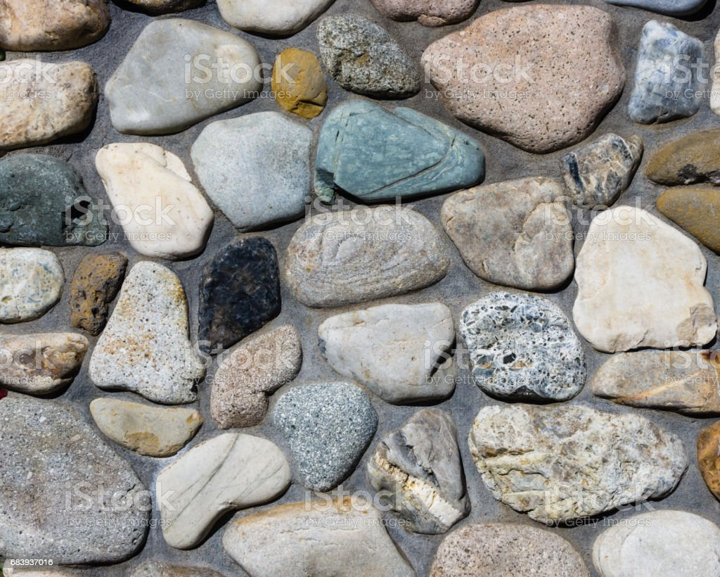River rock stone wall with mortar joints stock photo