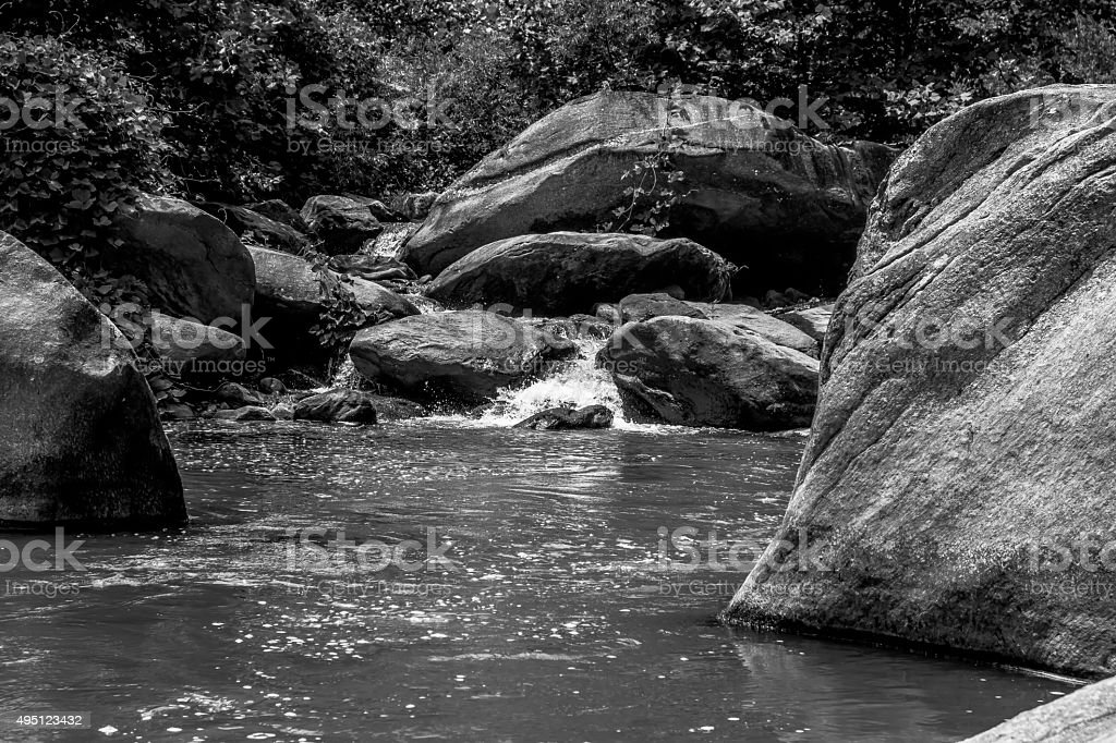 river stream flowing over rock formations in the mountains stock photo
