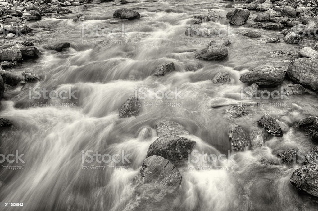 River water flowing through rocks at dawn stock photo