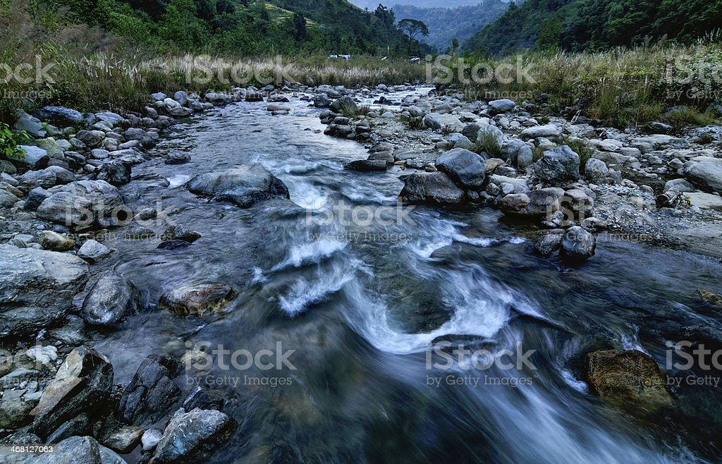 River water flowing through rocks at dawn, Sikkim, India royalty-free stock photo