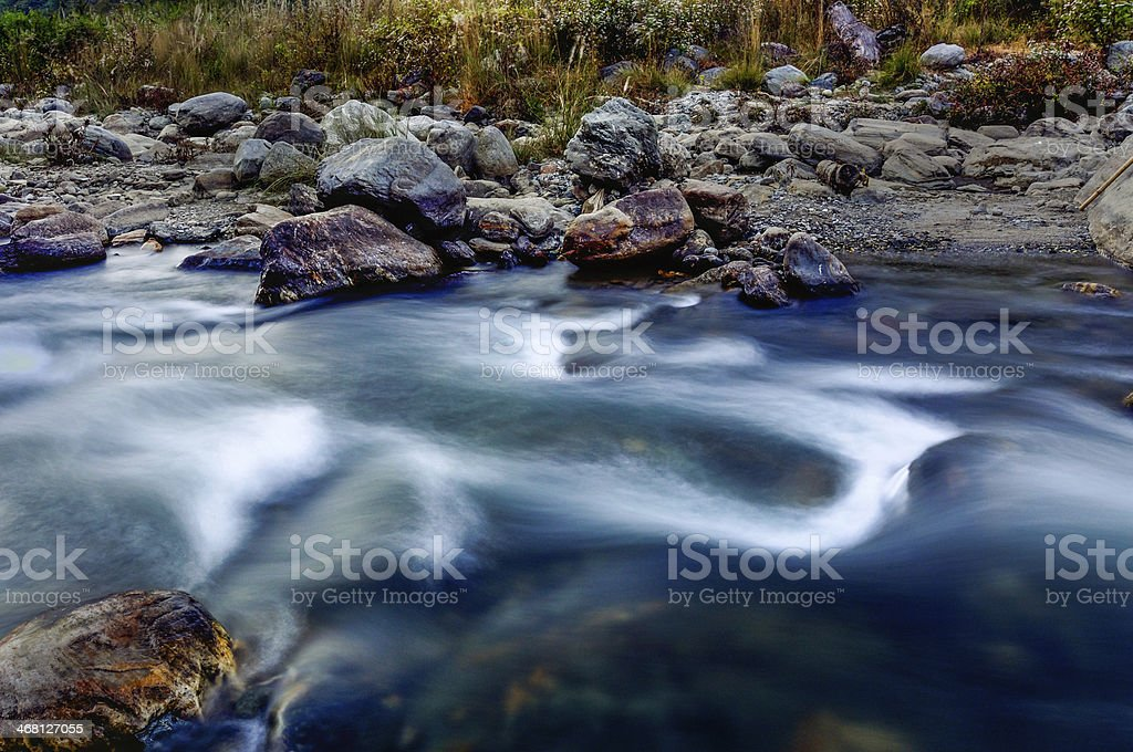 River water flowing through rocks at dusk, Sikkim, India royalty-free stock photo