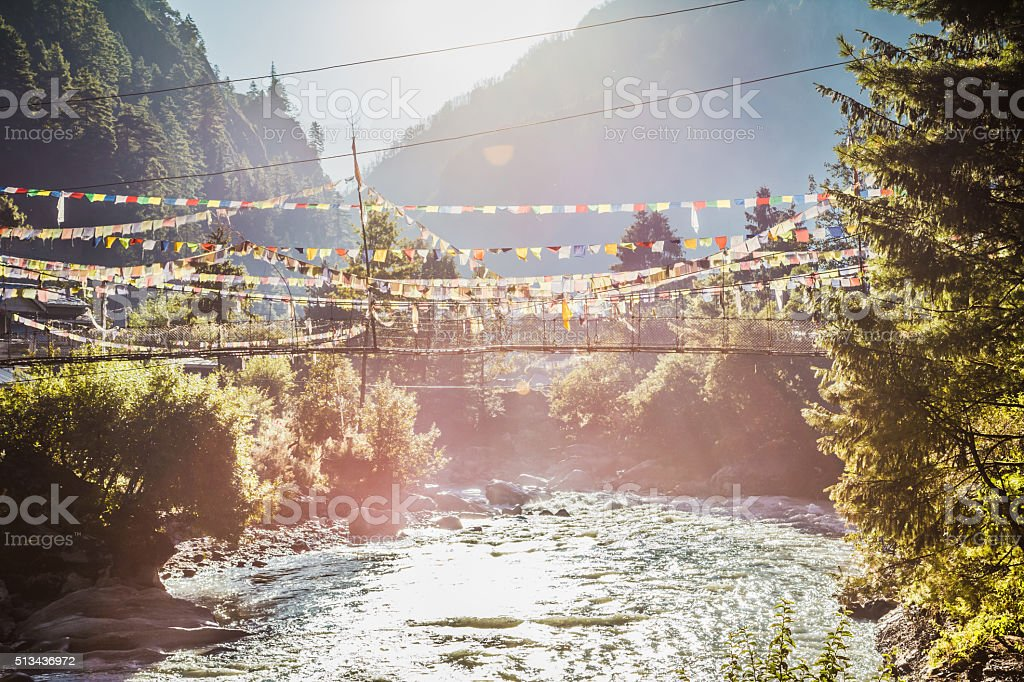 River with hanging pedestrian bridge and nepalese flags stock photo
