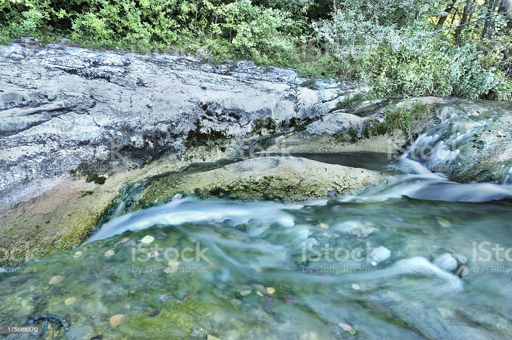 River with small cascade and leaves stock photo