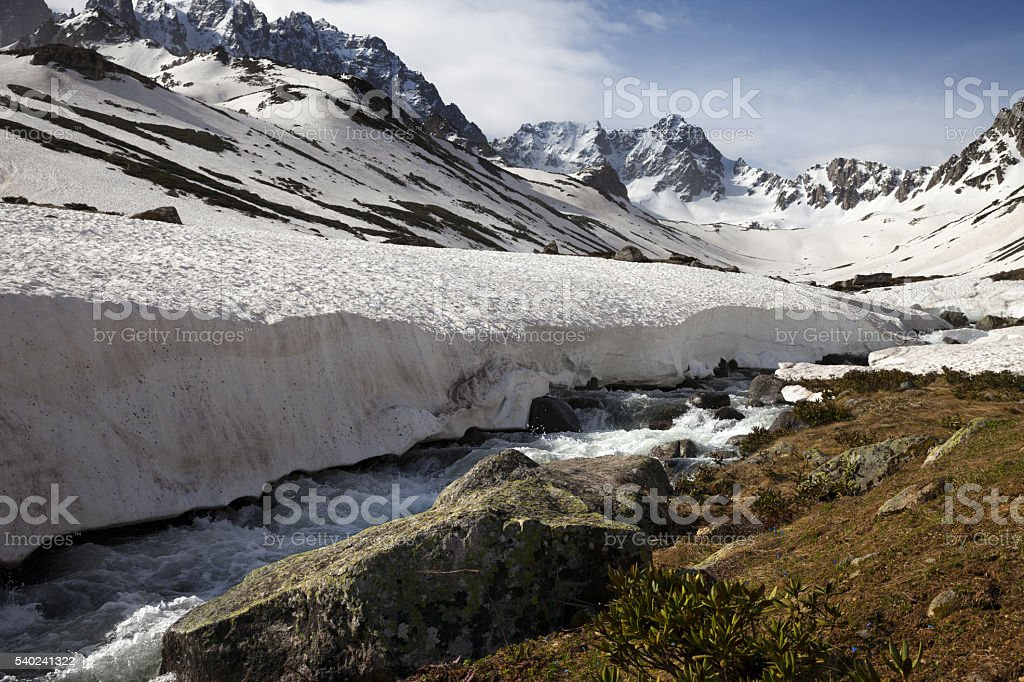 River with snow bridges in spring mountains at sun day stock photo
