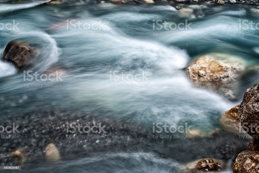 riverbed with blurred water sideview stock photo