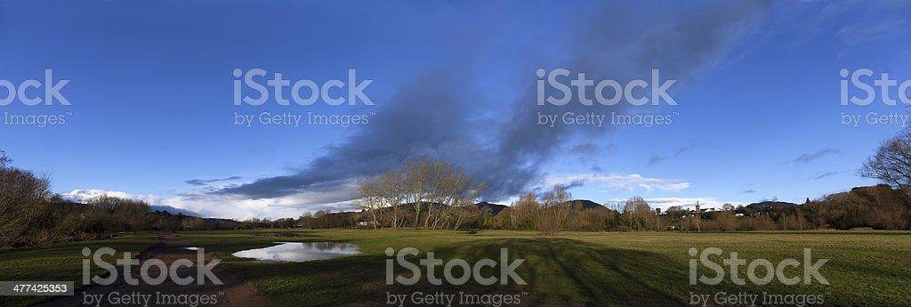Riverside prato con Panorama di nuvole foto stock royalty-free