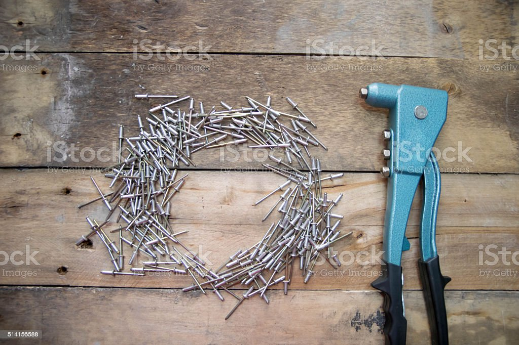 rivet pliers and rivet on wood stock photo