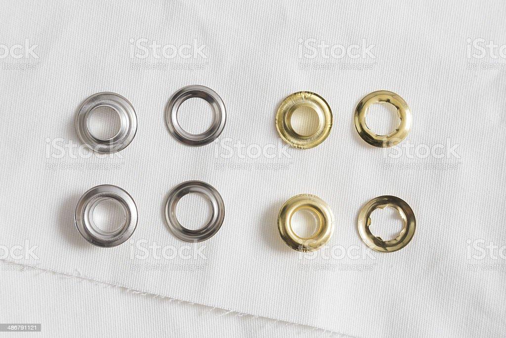 Rivets on light white cloth stock photo