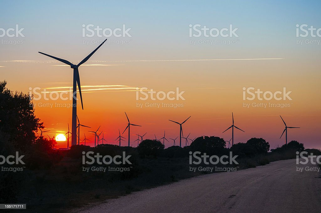 road across sun and silhouettes of wind generators royalty-free stock photo
