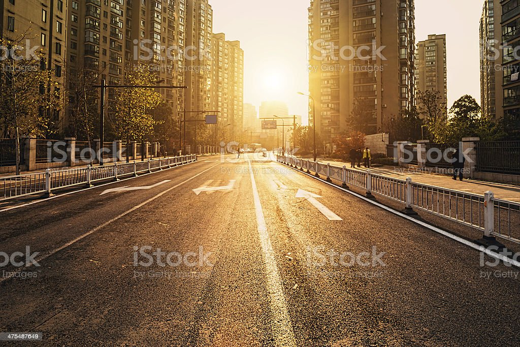 road and buildings at city with sunset stock photo