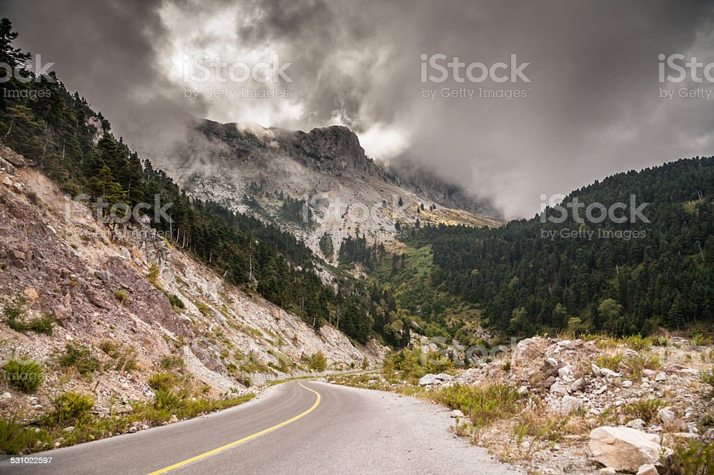 Road and stormy mountain landscape stock photo