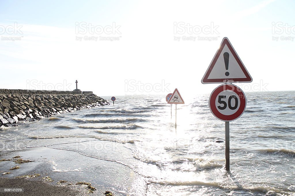 road and traffic signals flooded by tides in France stock photo