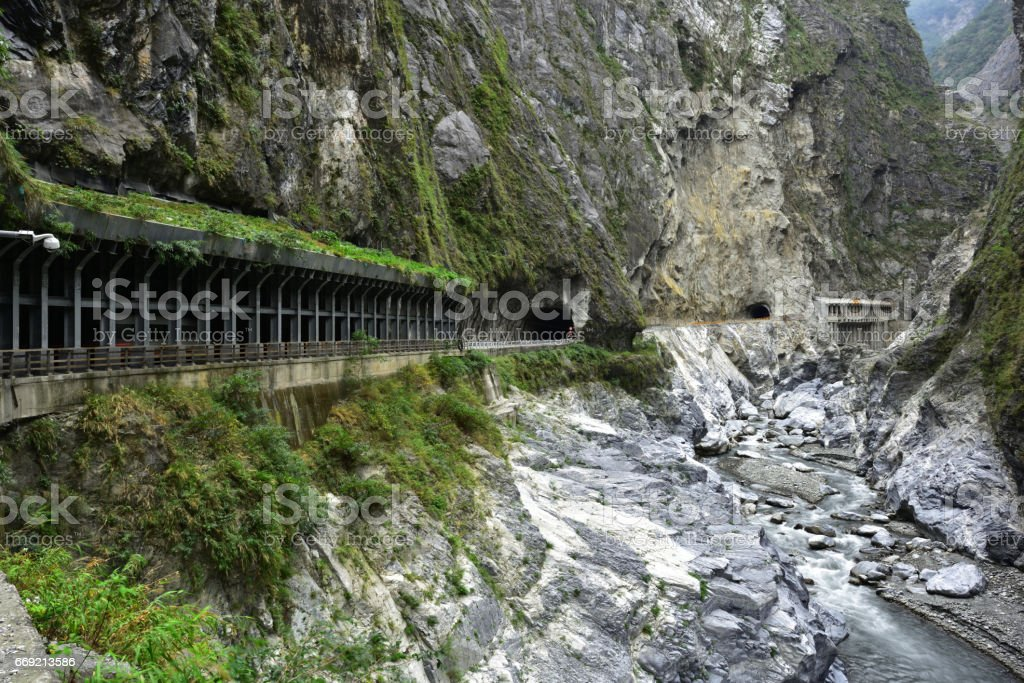 Road and tunnel pass through perpendicular cliff and mountain valley stock photo
