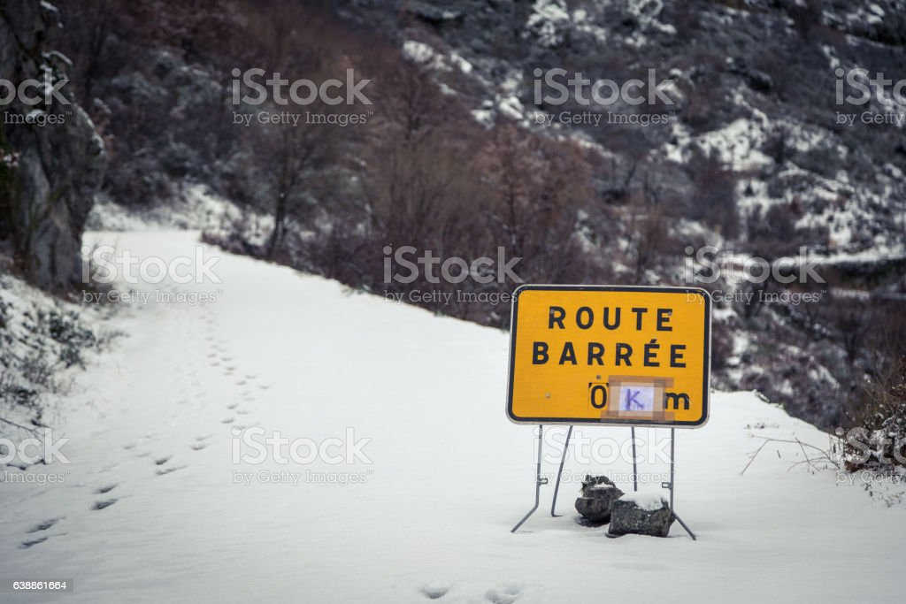 Road blocked sign on snow covered mountain road in Corsica stock photo