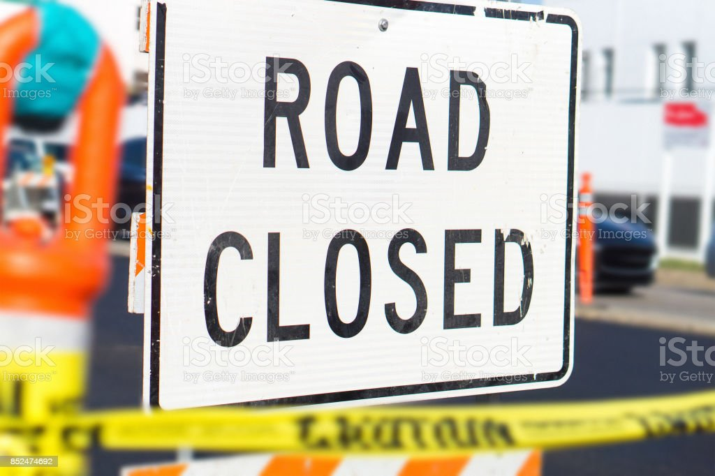 Road closed sign and block in a busy city street in the middle of traffic. Roadblock in a highway. stock photo
