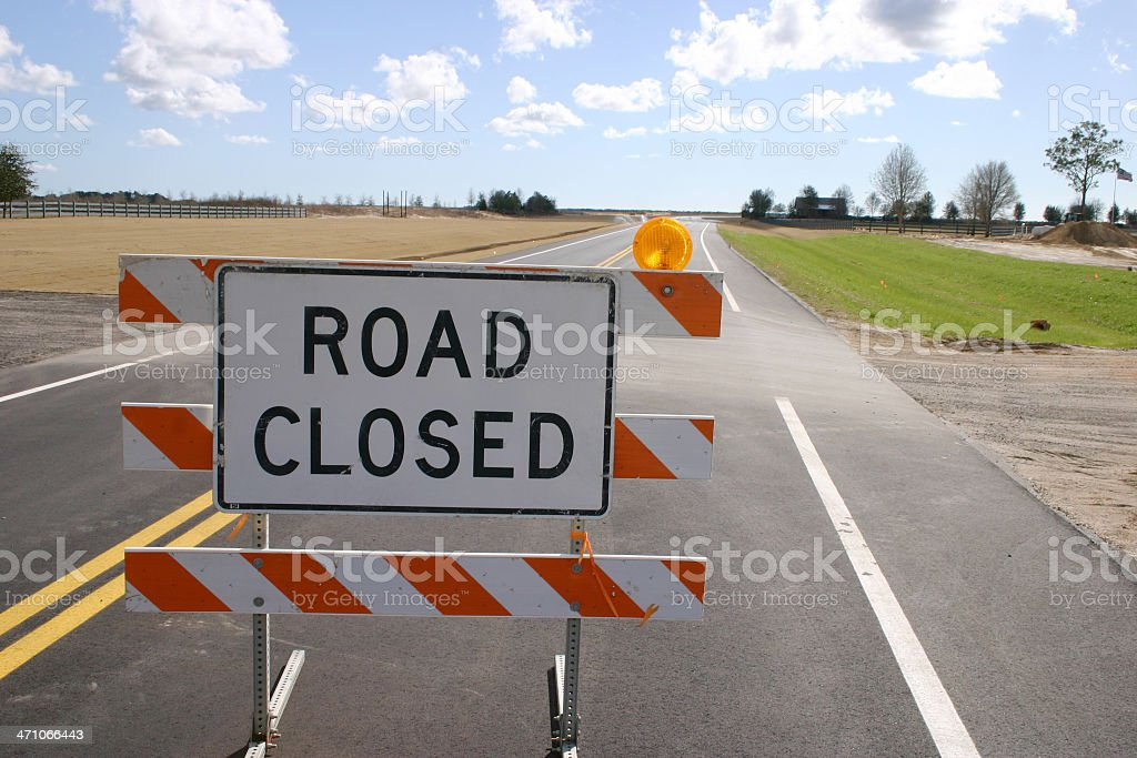 Road Closed sign in middle of empty road stock photo