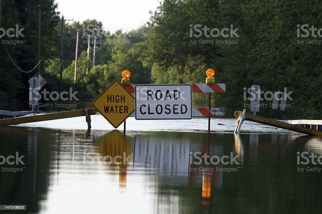 A road closure signage as water covers the road stock photo
