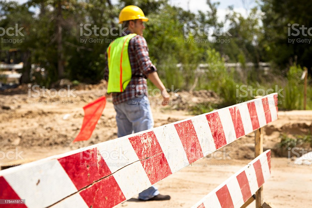 Road construction flagman.  Selective focus at mid point of barricade. royalty-free stock photo