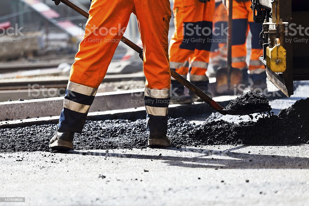 Road construction, worker with shovel stock photo