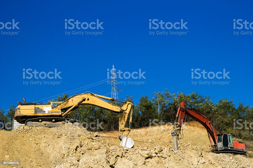 Road construction works. Heavy machinery - excavator and dump truck.. stock photo