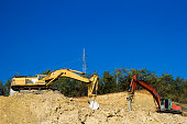 Road construction works. Heavy machinery - excavator and dump truck..