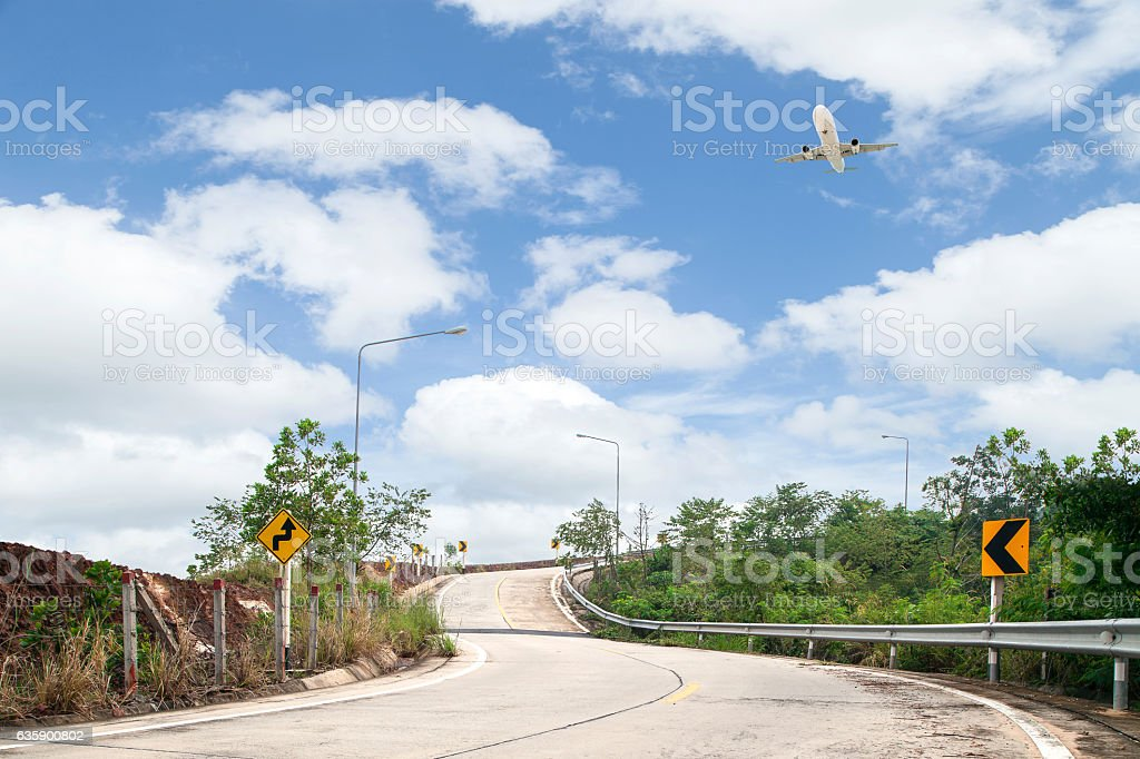 road curve and Airplane flying with blue sky background, stock photo