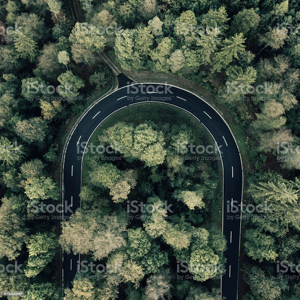 Road curve in the forest aerial view stock photo