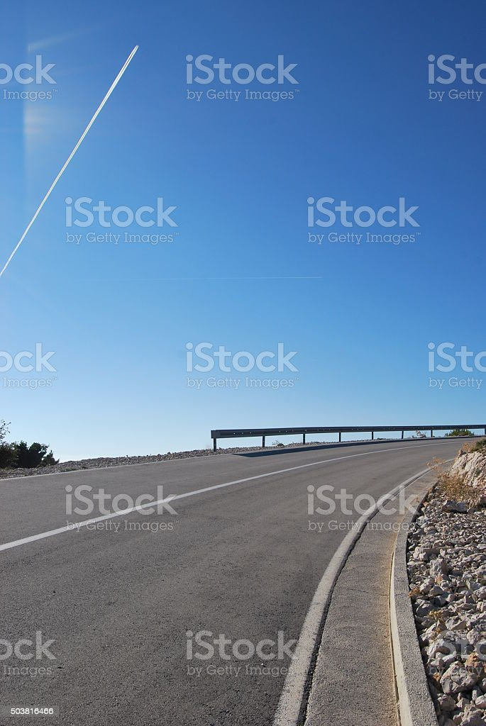 Road curve with trail of jet plane on blue sk stock photo