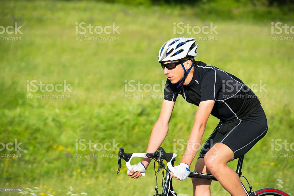 Road cyclist against the meadow stock photo