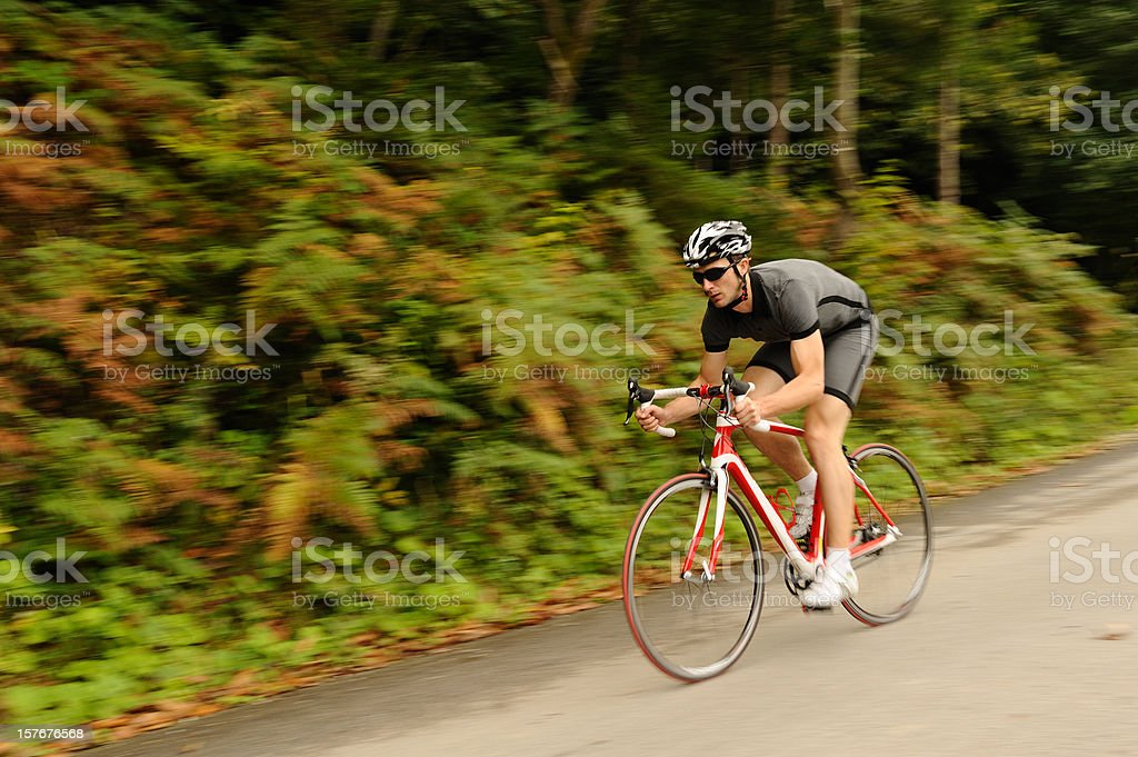 Road cyclist at downhill with blurred background stock photo