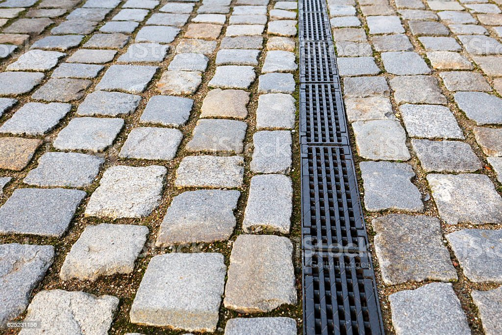 road from the old pavers and drainage system stock photo