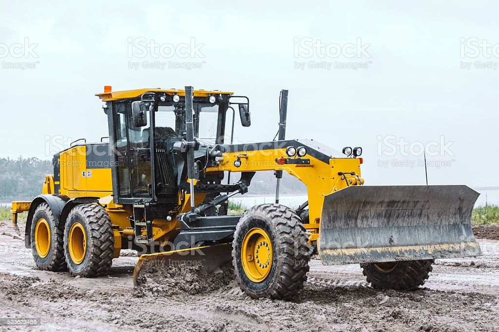 Road grader - heavy earth moving dirty stock photo