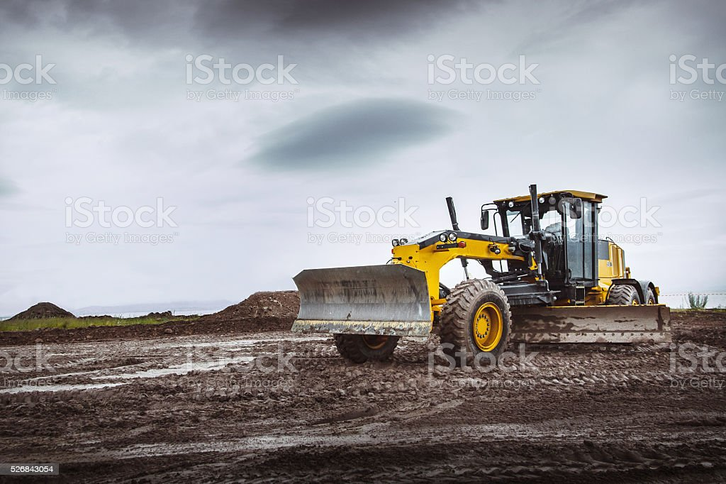 Road grader - heavy earth moving left dirty stock photo