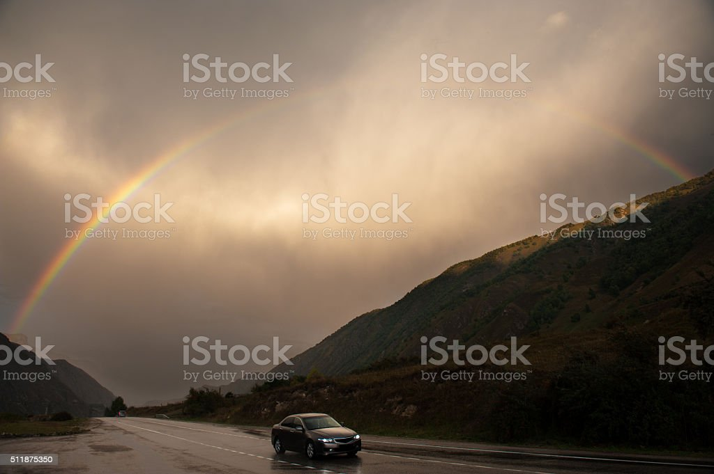 road highway car speed mountains cloudy rainbow travel stock photo