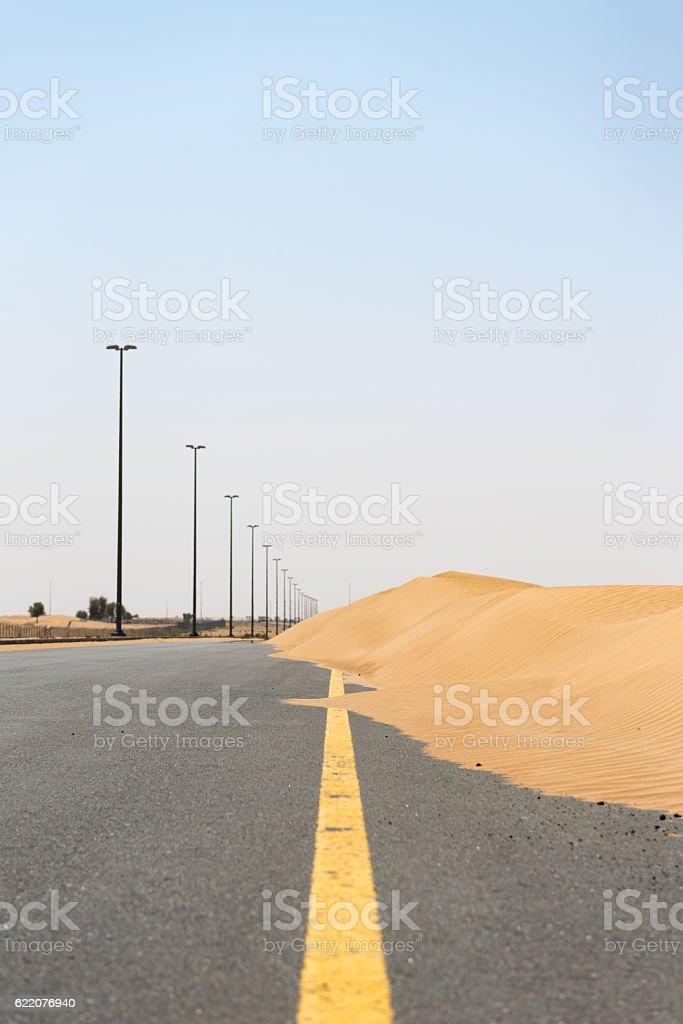 Road in desert blocked by sand dune stock photo