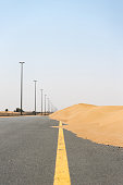 Road in desert blocked by sand dune