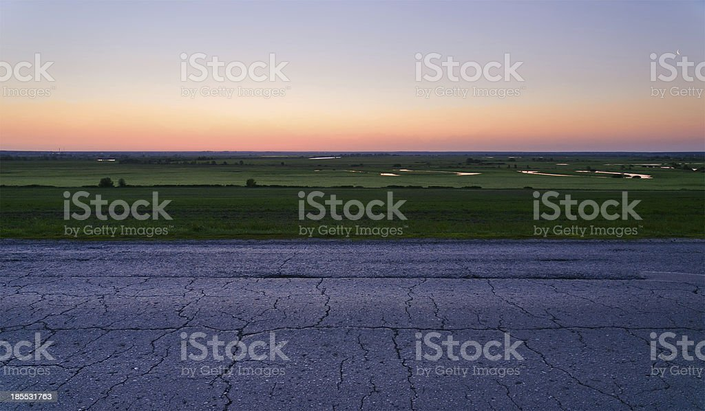 Road in field and cloudy sky royalty-free stock photo