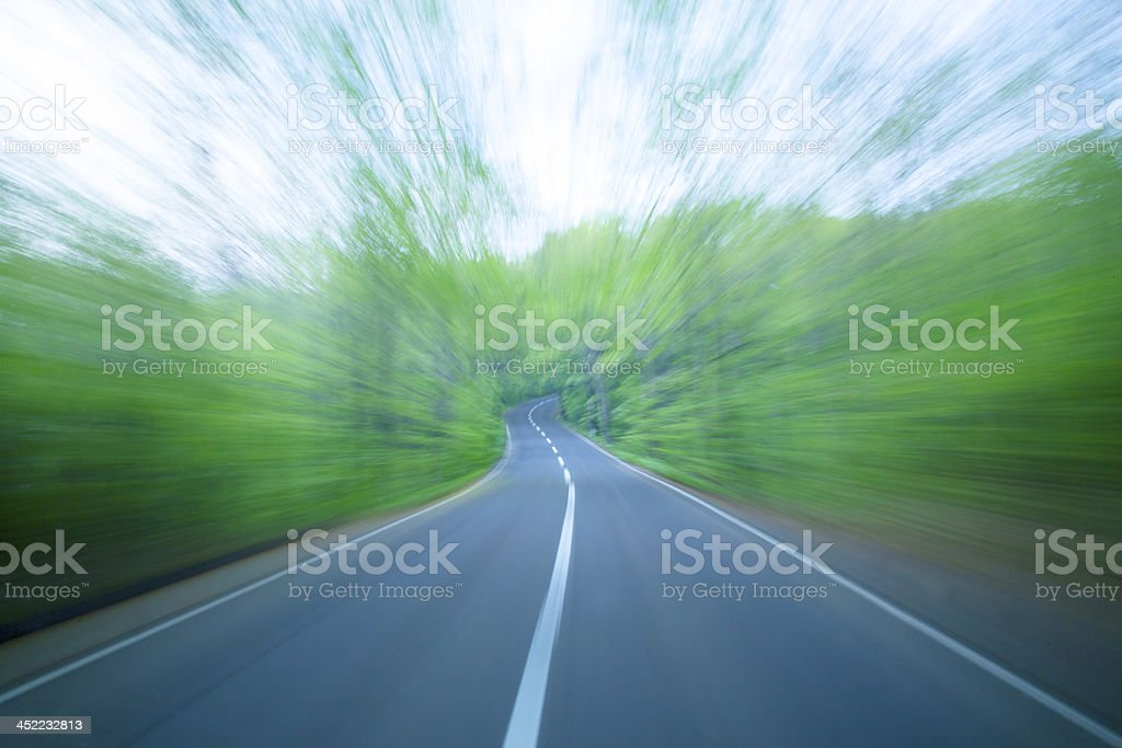 Road in motion blur at green forest royalty-free stock photo
