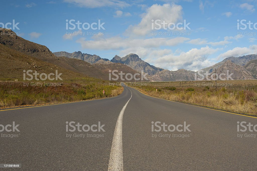 road in mountain landscape with cloudy sky, south africa stock photo