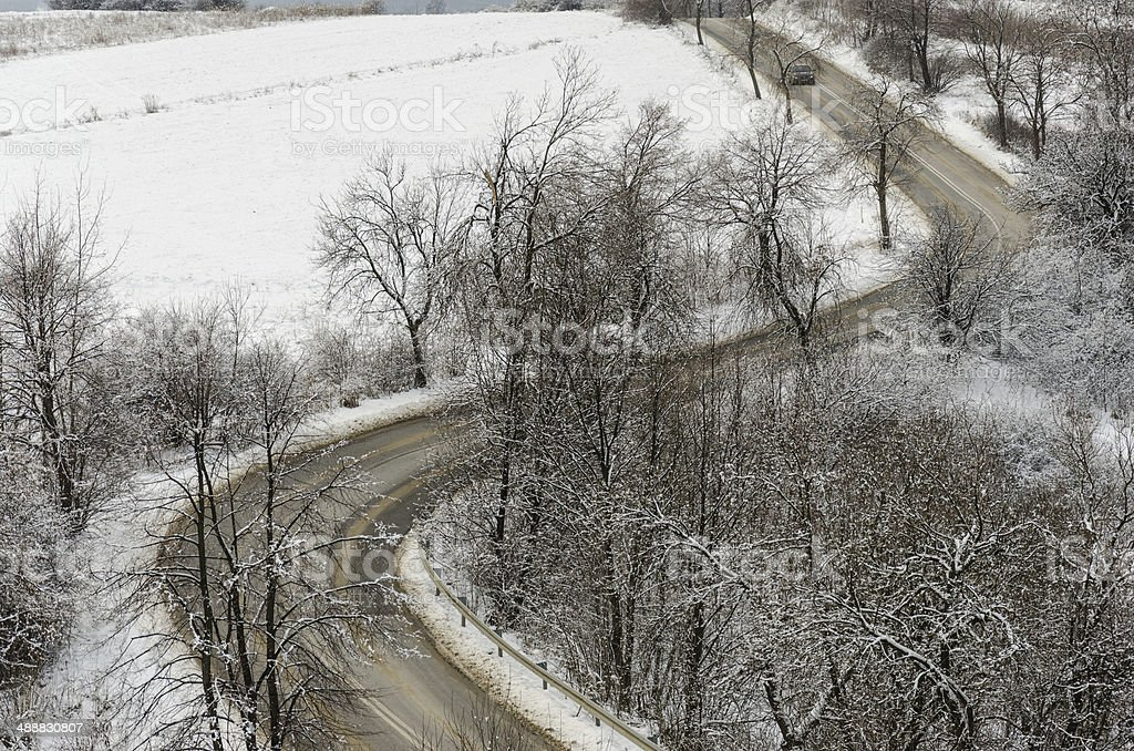 road in winter with curves seen from distance stock photo